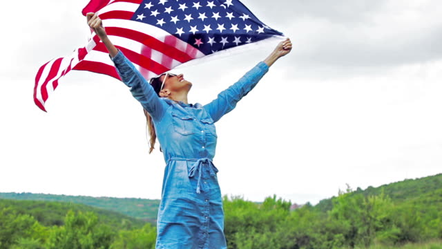 Beautiful woman carring U.S. flag with wide open hands