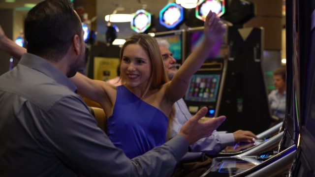 beautiful woman celebrating she just one at the slot machines sitting next to her partner hugging and smiling - casino winner stock videos & royalty-free footage