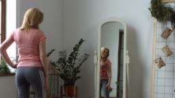 Beautiful woman checking her body shape in mirror