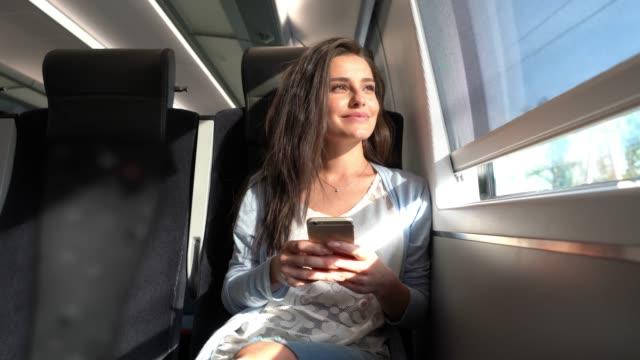 窓からの眺めを見ながらスマホで電車の中で通勤する美人女性 - 乗る点の映像素材/bロール