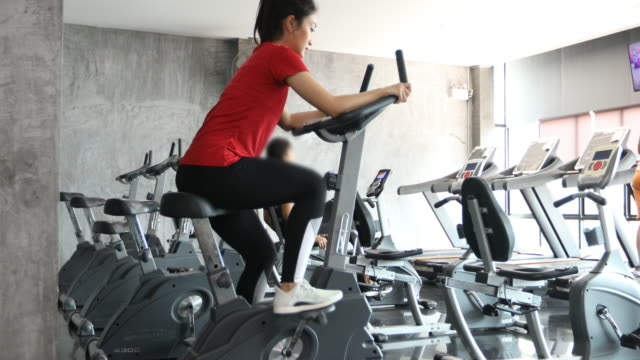 beautiful woman cycling on the exercise bike in the gym - exercise bike stock videos & royalty-free footage