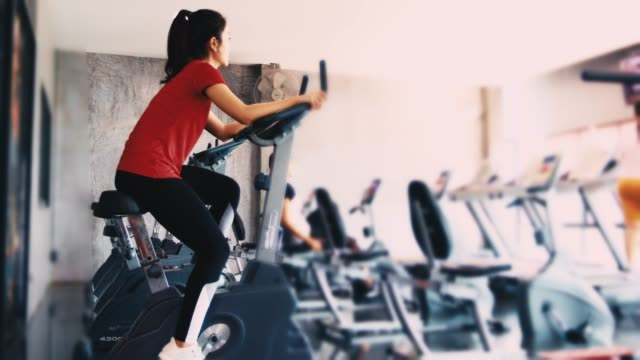 beautiful woman cycling on the exercise bike in the gym - cardiovascular exercise stock videos & royalty-free footage