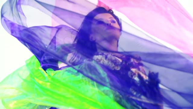 Schöne Frau Tanzen im farbiger Seide. Zeitlupe.