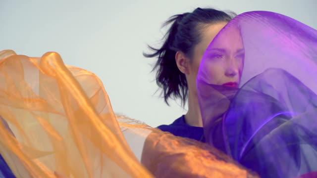 vidéos et rushes de belle femme danse en soie de couleur vive. ralenti. - châle