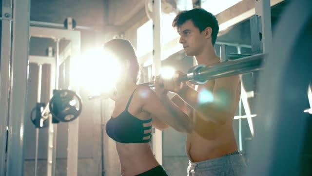 vídeos y material grabado en eventos de stock de mujer hermosa haciendo levantamiento de pesas en gimnasio con entrenador personal - press de banca