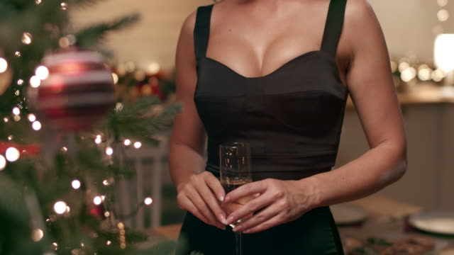 beautiful woman drinking champagne against christmas holiday garland lights - christmas lights stock videos & royalty-free footage