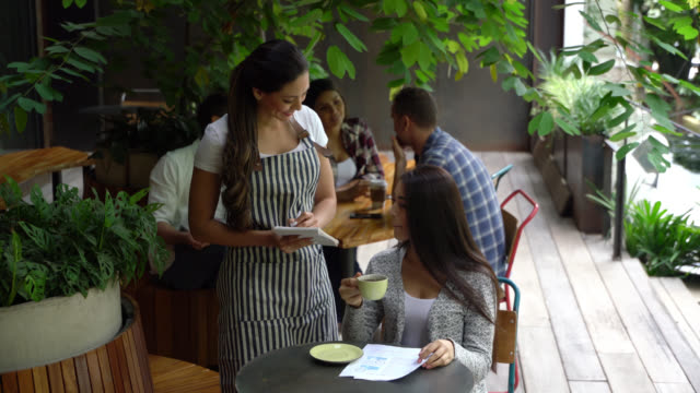 vídeos de stock e filmes b-roll de beautiful woman drinking coffee and ordering something from menu while waitress takes her order smiling - empregada de mesa