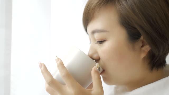 窓のそばでコーヒーを飲む美しい女性 - 中国人点の映像素材/bロール
