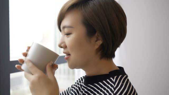 窓のそばでコーヒーを飲む美しい女性 - ノミ点の映像素材/bロール
