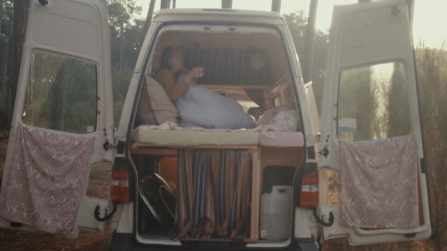 beautiful woman drinking coffee in her motor home in the forest in the south of france. - van vehicle stock videos and b-roll footage