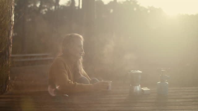 Beautiful woman drinking hot coffee outside at picnic table in the pine forest in the South of France at sunrise.