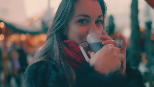 beautiful woman drinking mulled wine at christmas market - marktstand stock-videos und b-roll-filmmaterial
