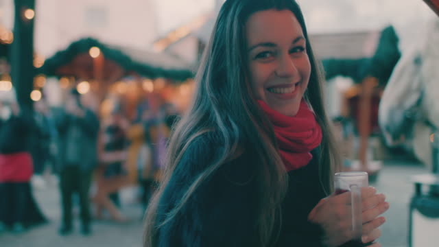 beautiful woman drinking mulled wine at christmas market - 温かい飲み物点の映像素材/bロール