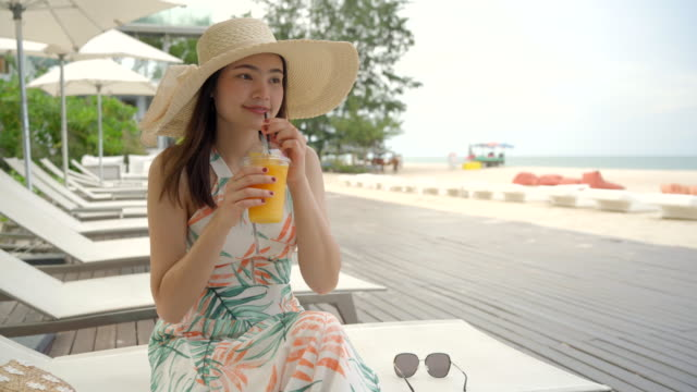 beautiful woman drinking orange juice on the beach. - holding stock videos & royalty-free footage