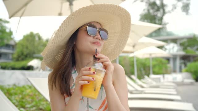 beautiful woman drinking orange juice on the beach. - juice drink stock videos & royalty-free footage