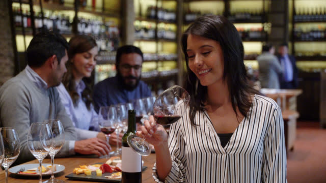 beautiful woman drinking wine at a cellar while facing camera smiling - party host stock videos & royalty-free footage
