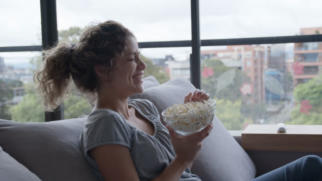 beautiful woman during pandemic lockdown at home watching a comedy movie while enjoying pop corn - mental wellbeing stock videos & royalty-free footage