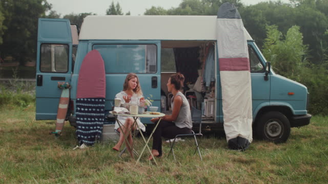 stockvideo's en b-roll-footage met beautiful woman eating croissants in front of van/camping in the morning - homoseksueel persoon