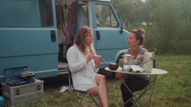 vídeos y material grabado en eventos de stock de beautiful woman eating granola in field in front of van/camping in the morning - cereal