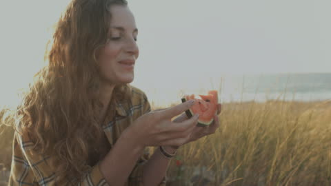 vidéos et rushes de beautiful woman eating water melon in sunshine on a sand dune on beach at atlantic ocean in the south of france - freshness
