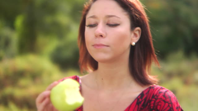 HD DOLLY: Beautiful woman eats an apple in the park