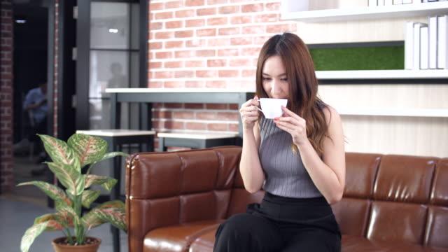 schöne frau genießen kaffee trinken in coffee shop, kaffeepause - nur junge frauen stock-videos und b-roll-filmmaterial