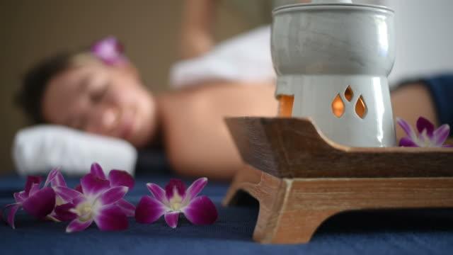 Beautiful woman enjoying aromatherapy oil massage in spa salon.