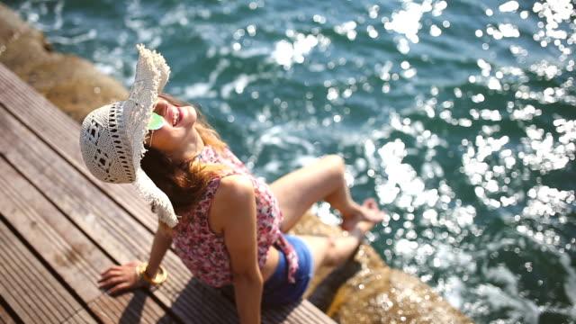 vídeos de stock e filmes b-roll de beautiful woman enjoying by the sea - chapéu