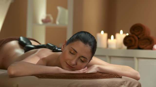 hd: beautiful woman enjoying lastone therapy - massage table stock videos & royalty-free footage