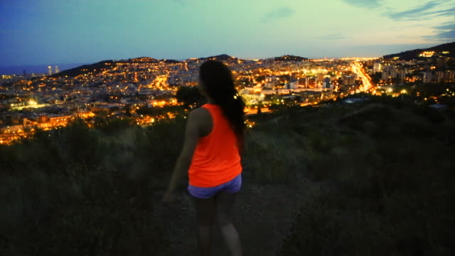 Beautiful woman enjoying nature walk on top of Barcelona mountains contemplating the city at dusk with elevated point of view during summer good vibes in a romantic place.
