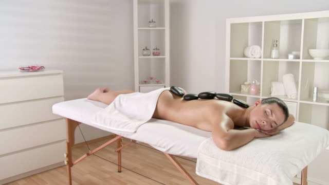 hd crane: beautiful woman enjoying relaxing therapy - lastone therapy stock videos and b-roll footage