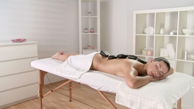 vídeos de stock, filmes e b-roll de grou hd: mulher bonita desfrutando de terapia relaxante - lastone therapy