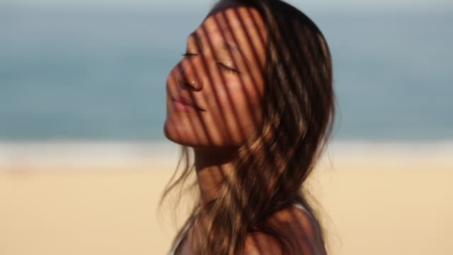 beautiful woman enjoying the sunshine with closed eyes at deserted beach in the south of france. - augen geschlossen stock-videos und b-roll-filmmaterial