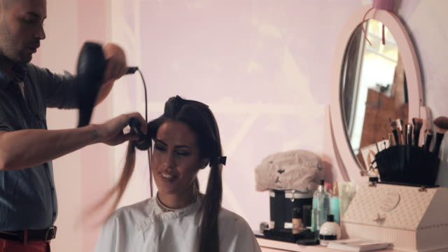 beautiful woman enjoying while making a hairstyle at hairdresser's. - blow drying hair stock videos and b-roll footage