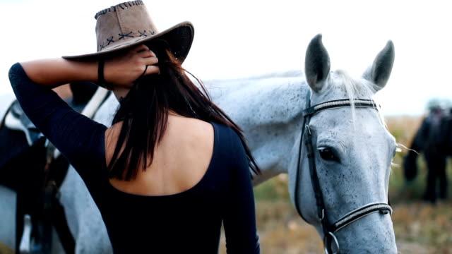美しい女性は、彼女の白い馬と彼女の時間を楽しんでいます - 乗馬点の映像素材/bロール