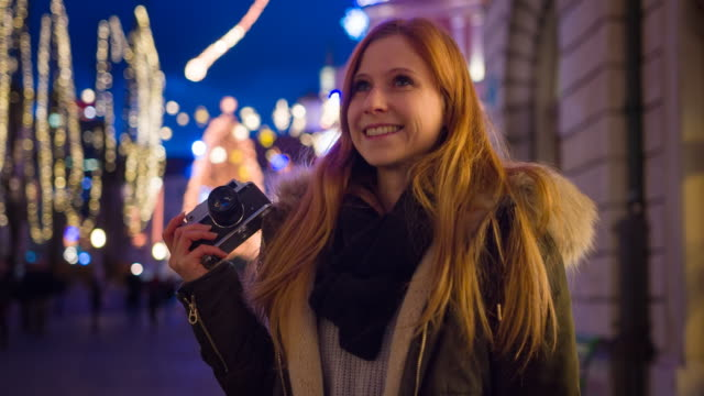 vídeos de stock e filmes b-roll de beautiful woman exploring christmas in the city, admiring brightly lit and decorated streets - brightly lit