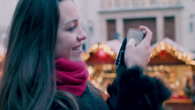 beautiful woman filming stalls at christmas market with mobile phone - souvenir stock videos and b-roll footage