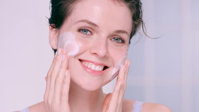 beautiful woman gently rubbing a foam cleanser into her skin - routine stock-videos und b-roll-filmmaterial