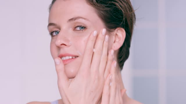 beautiful woman gently rubbing a foam cleanser into her skin - positive emotion stock videos & royalty-free footage