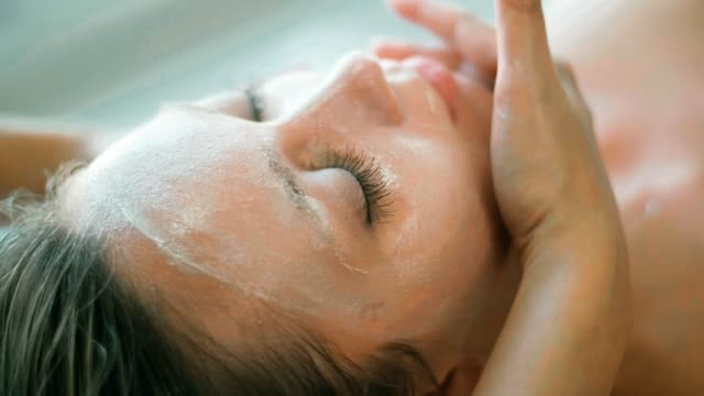 beautiful woman getting a facial massage in spa - facial massage stock videos and b-roll footage
