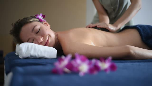 vídeos y material grabado en eventos de stock de hermosa mujer conseguir una piedra caliente del masaje en el salón de spa. - lastone therapy