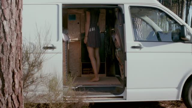 vídeos de stock e filmes b-roll de beautiful woman getting dressed/changing clothes in the back of her van in the morning in the south of france. - carrinha veículo