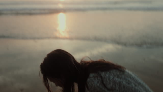 vidéos et rushes de beautiful woman going for walk on deserted beach in the south of france during sunset picking up shells and rocks - coquille et coquillage