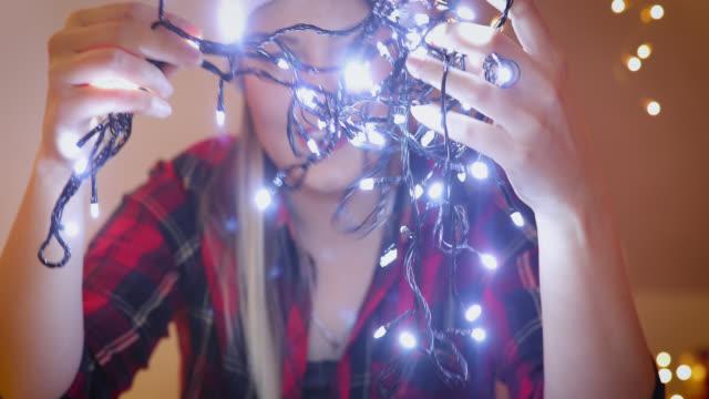 vídeos de stock e filmes b-roll de beautiful woman hanging christmas lights. holiday concept - enfeitar a árvore de natal
