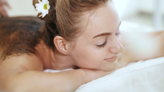 beautiful woman having back massage with coffee - dorso umano video stock e b–roll