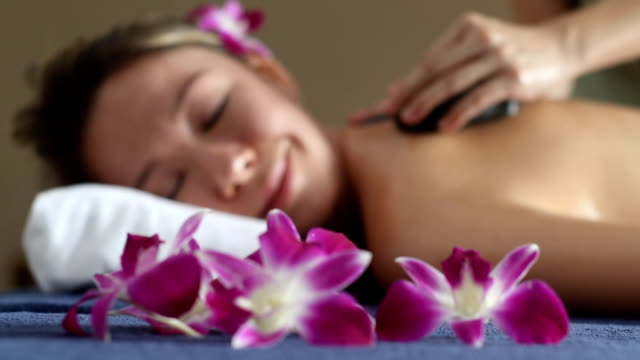 Beautiful woman having relaxing in hot stones massage