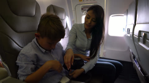 beautiful woman helping a little boy with his seat belt waiting for the plane to take off - vehicle interior stock videos & royalty-free footage