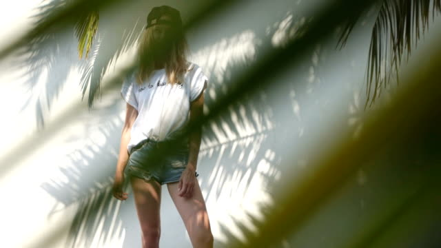 Beautiful woman hiding behind palm leaf. Summer games