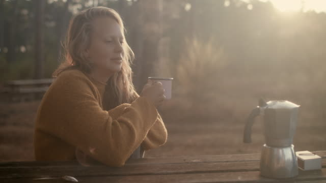 Beautiful woman holding coffee mug with steaming fresh coffee at picnic table in the forest in the morning in the South of France.
