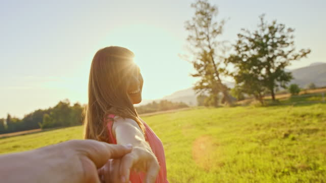 stockvideo's en b-roll-footage met pov beautiful woman holding hands with man and turning while walking in the sunny meadow - sunny